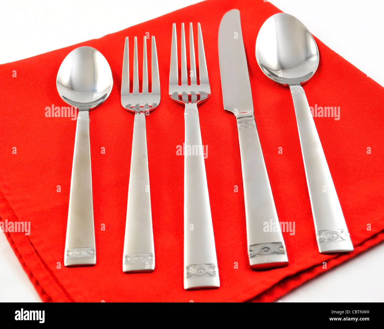 silverware set on a red napkin - Stock Image