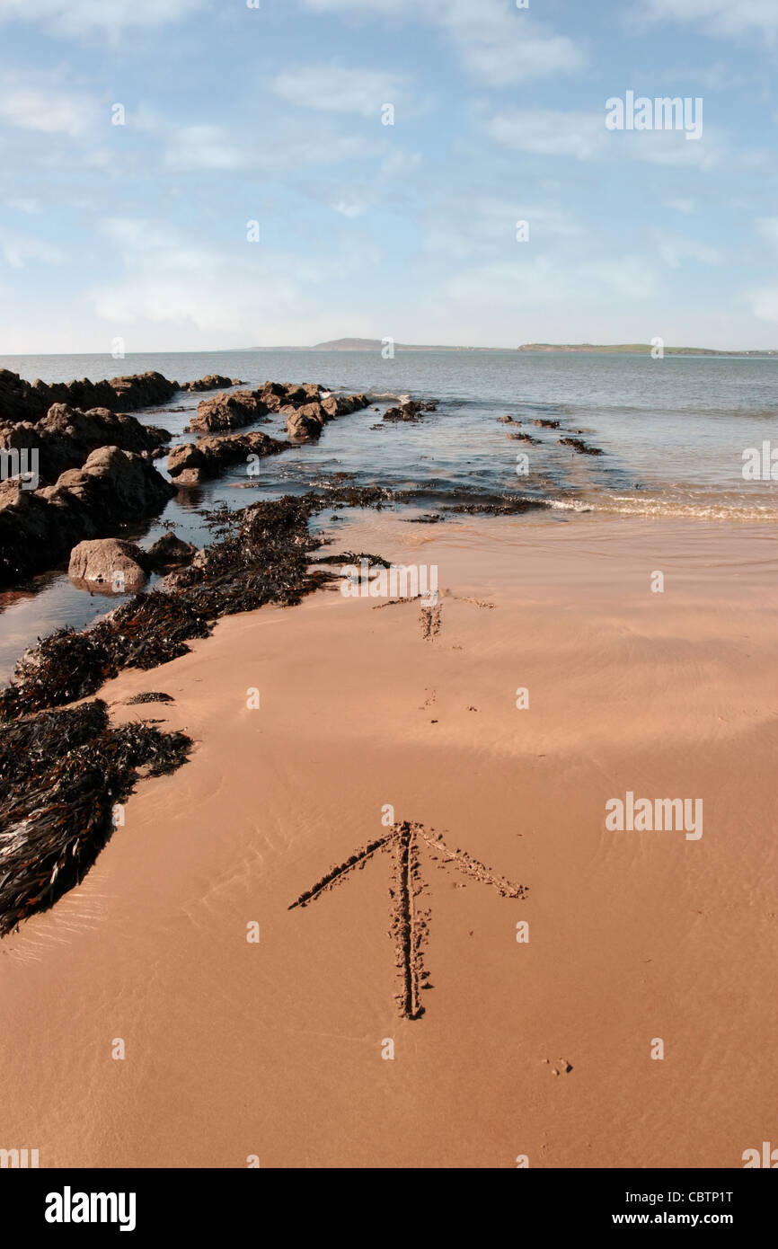 arrows giving directions inscribed on the beach with waves in the background on a hot sunny day - Stock Image