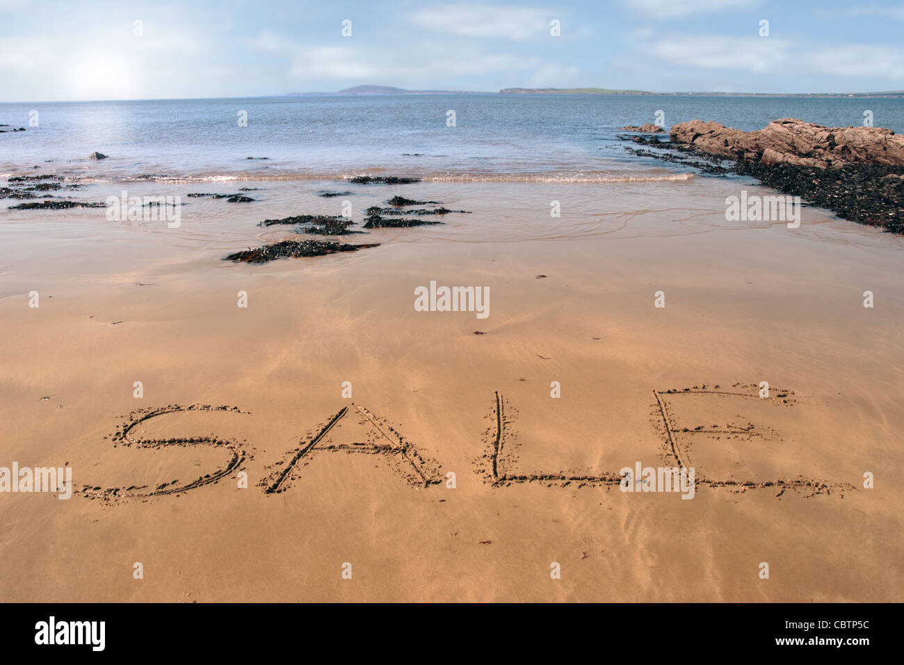 sale inscribed on the beach with waves in the background on a hot sunny day - Stock Image