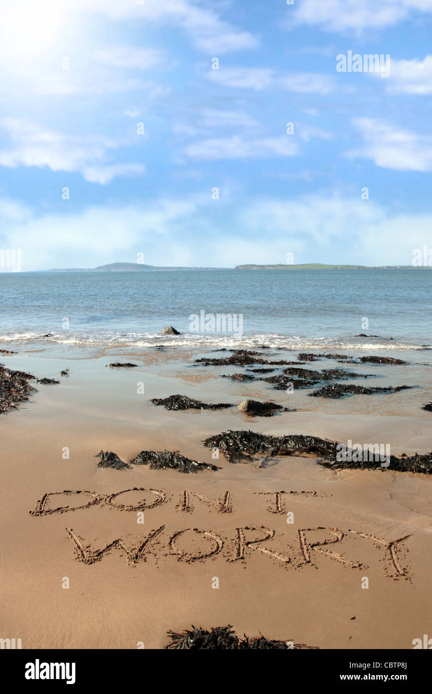 don't worry inscribed on the beach with waves in the background on a hot sunny day - Stock Image