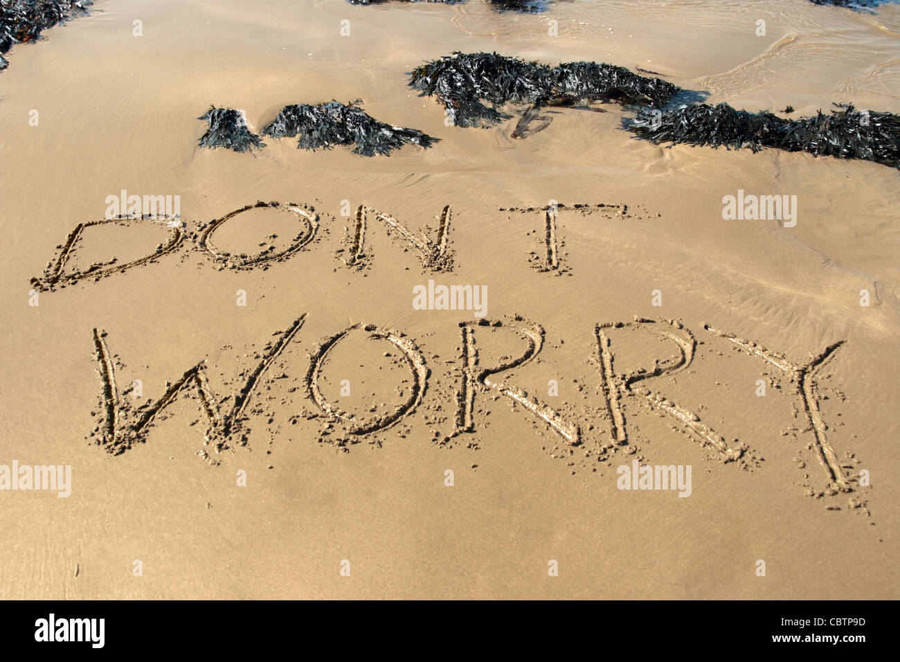 dont worry inscribed on the beach with waves in the background on a hot sunny day - Stock Image
