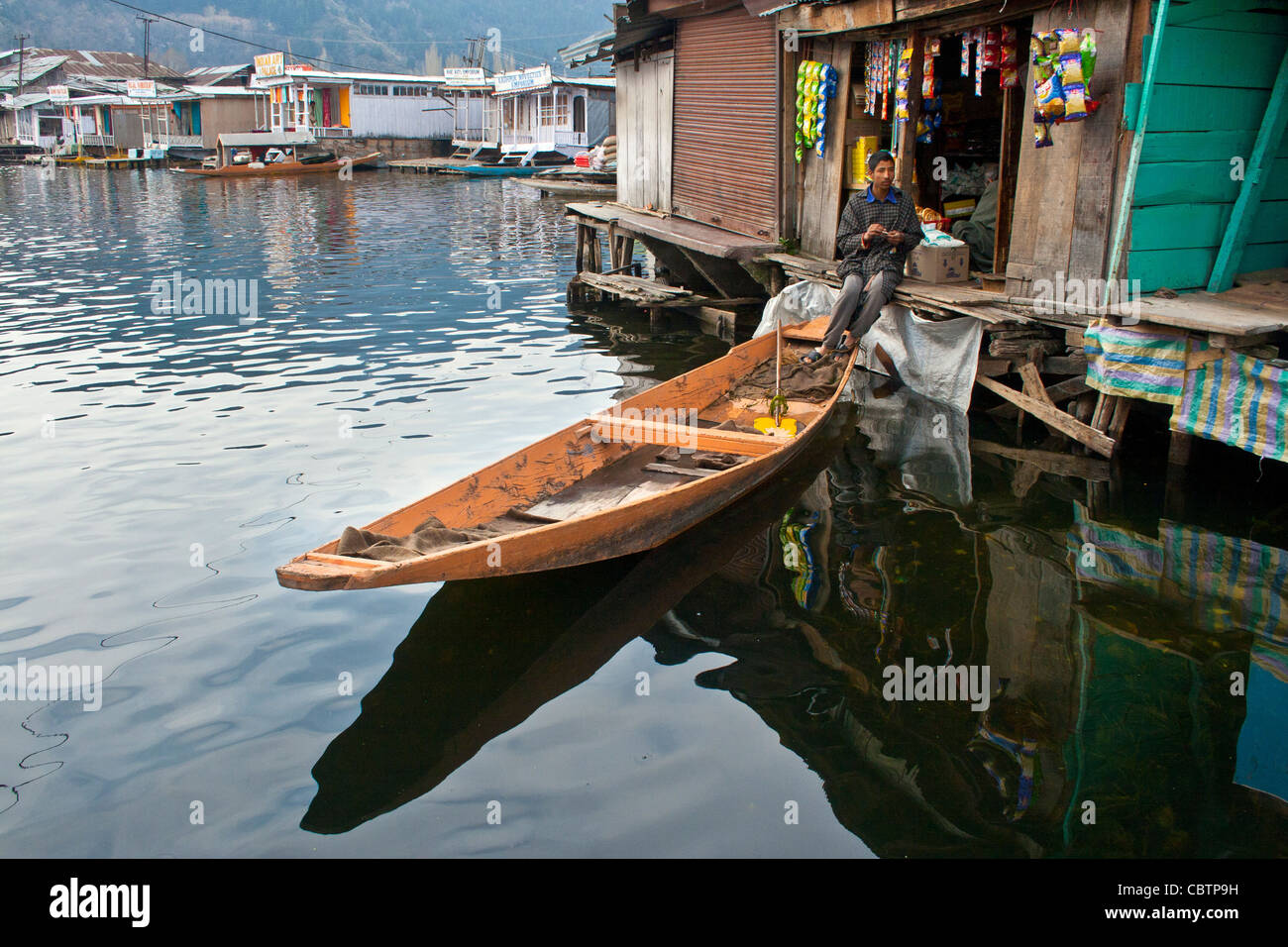 A Kashmiri man sits at his shop in the floating market of Dal Lake - Stock Image