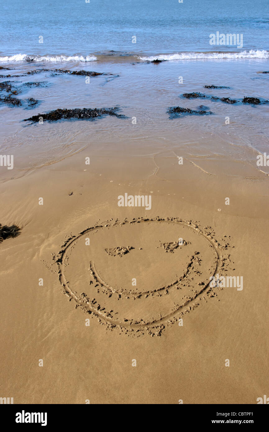 a smiley face icon inscribed on the beach with waves in the background on a hot sunny day - Stock Image