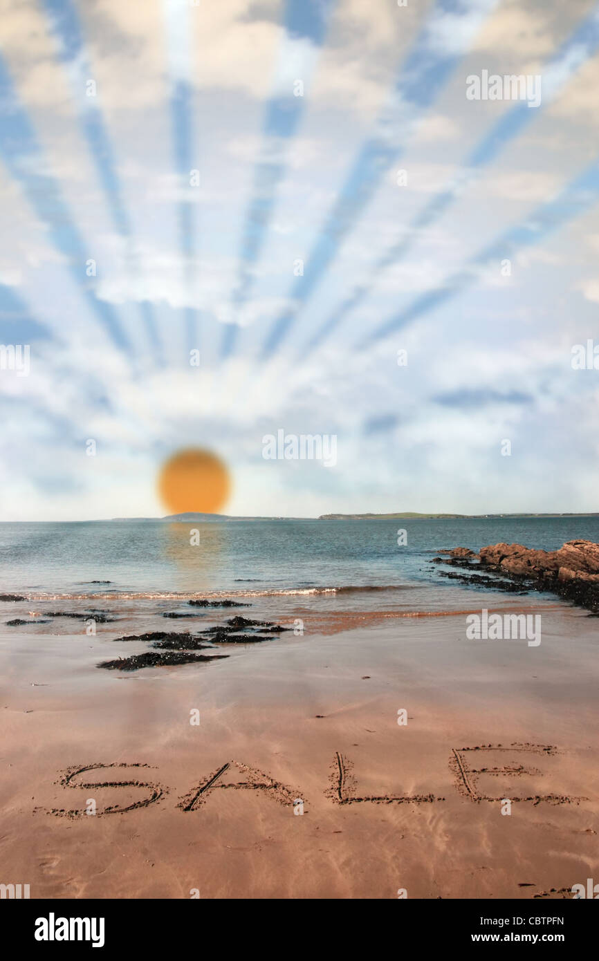 sale inscribed on the beach with waves and sunshine and rays in the background on a hot sunny day - Stock Image