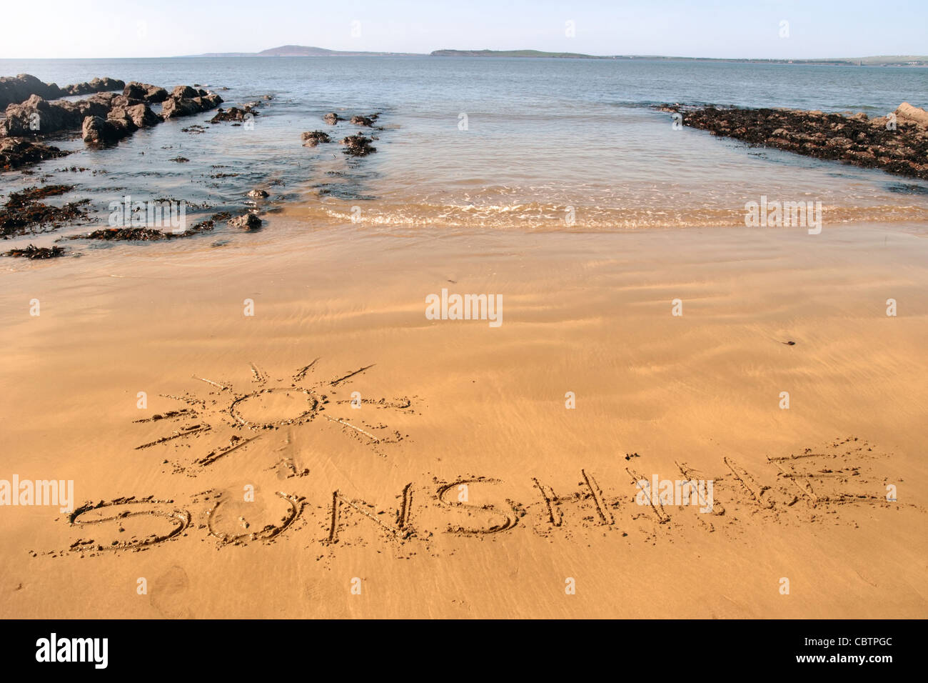 a sunshine icon inscribed on the beach with waves in the background on a hot sunny day - Stock Image