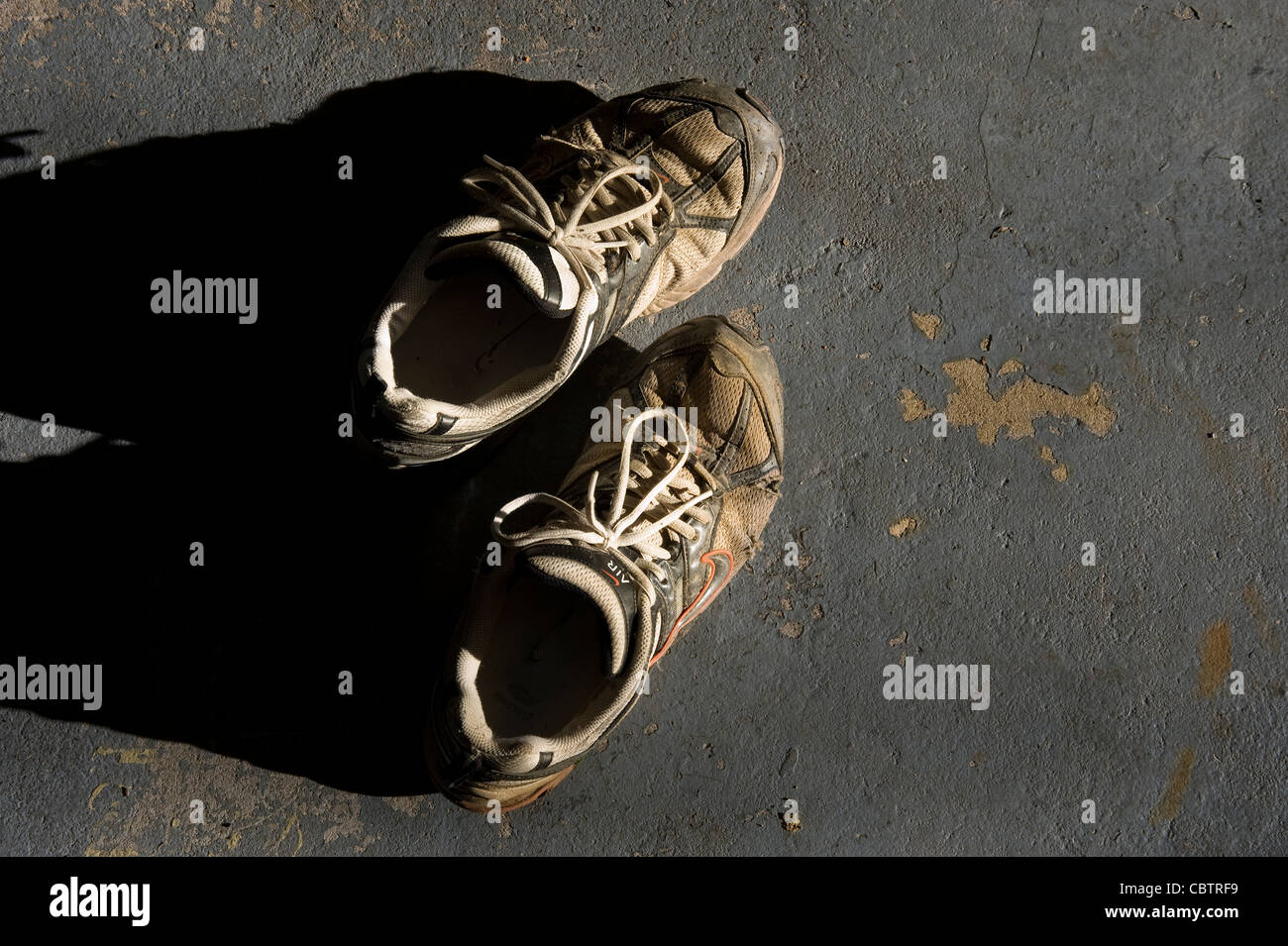 Old Dirty Sneakers Shoes, In Sunlight, Concrete Floor - Stock Image