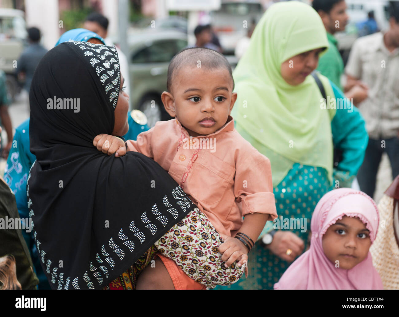A woman carryin his baby boy, Little India, Singapore - Stock Image