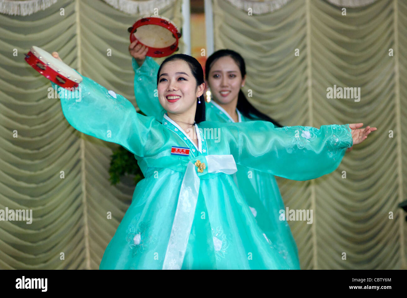 North Korean waitresses dance w/ Tambourines during a traditional North Korean performance, Pyongyang Restaurant, - Stock Image