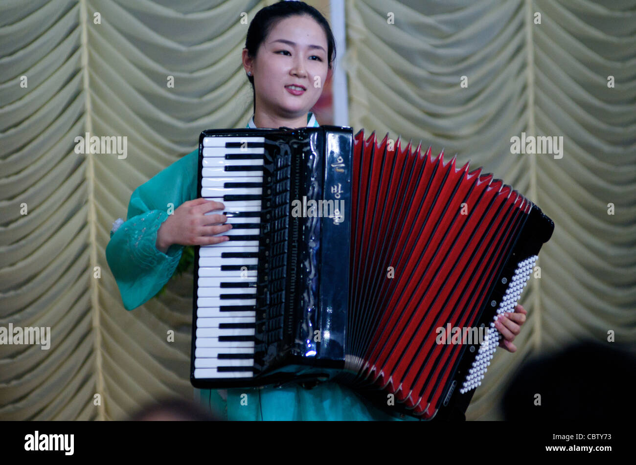 North Korean waitress plays an accordion during traditional North Korean performance, Pyongyang Restaurant, Phnom - Stock Image