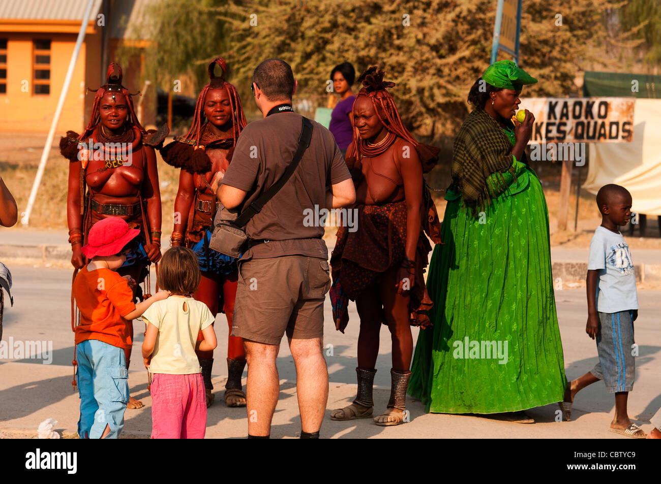 Himbas in the street of Opuwo town being photografed by tourists, Kunene, northern Namibia - Stock Image