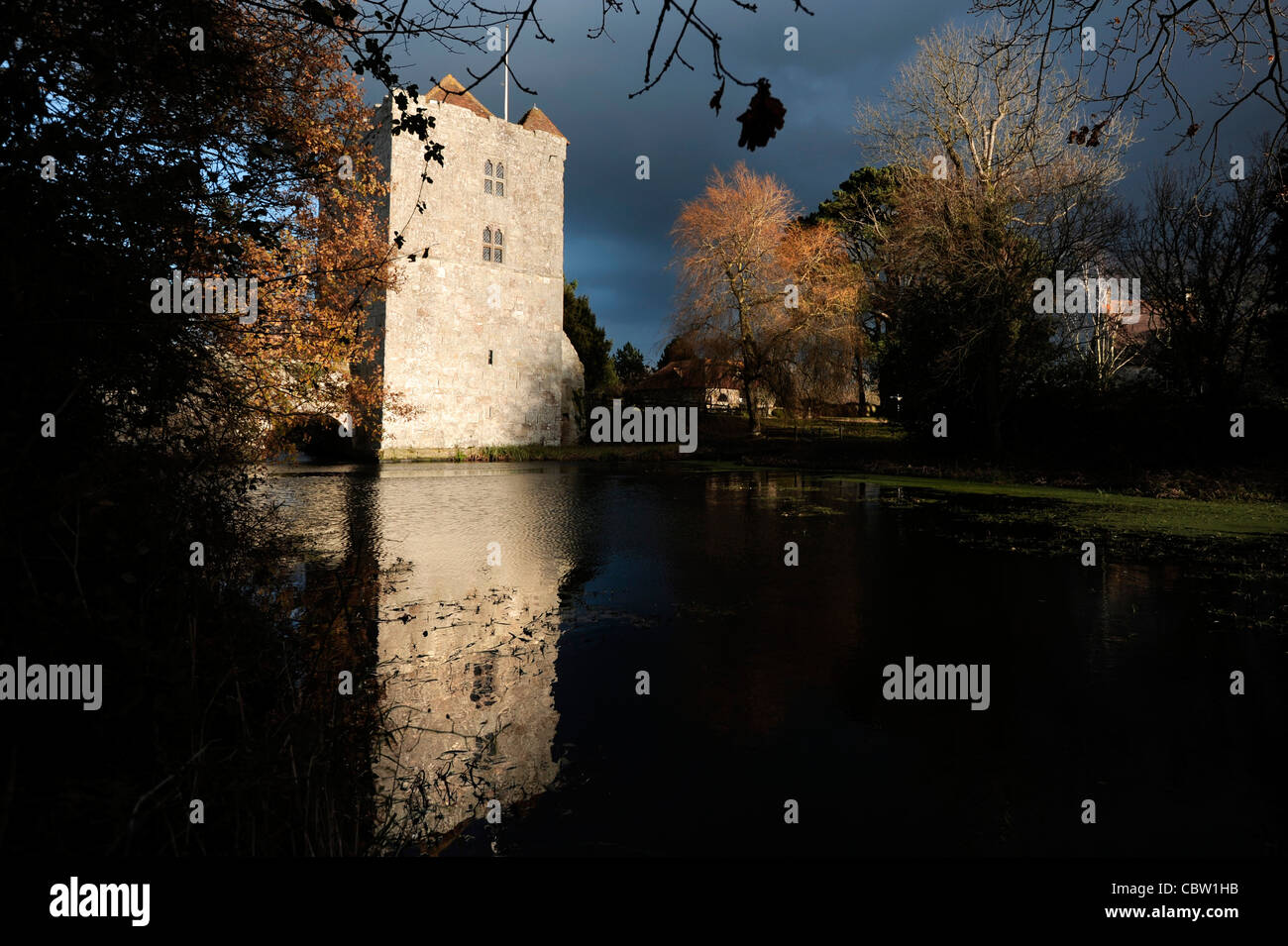 A shaft of golden sunlight illuminates the gate house tower at Michelham Priory, East Sussex, on a stormy day. - Stock Image