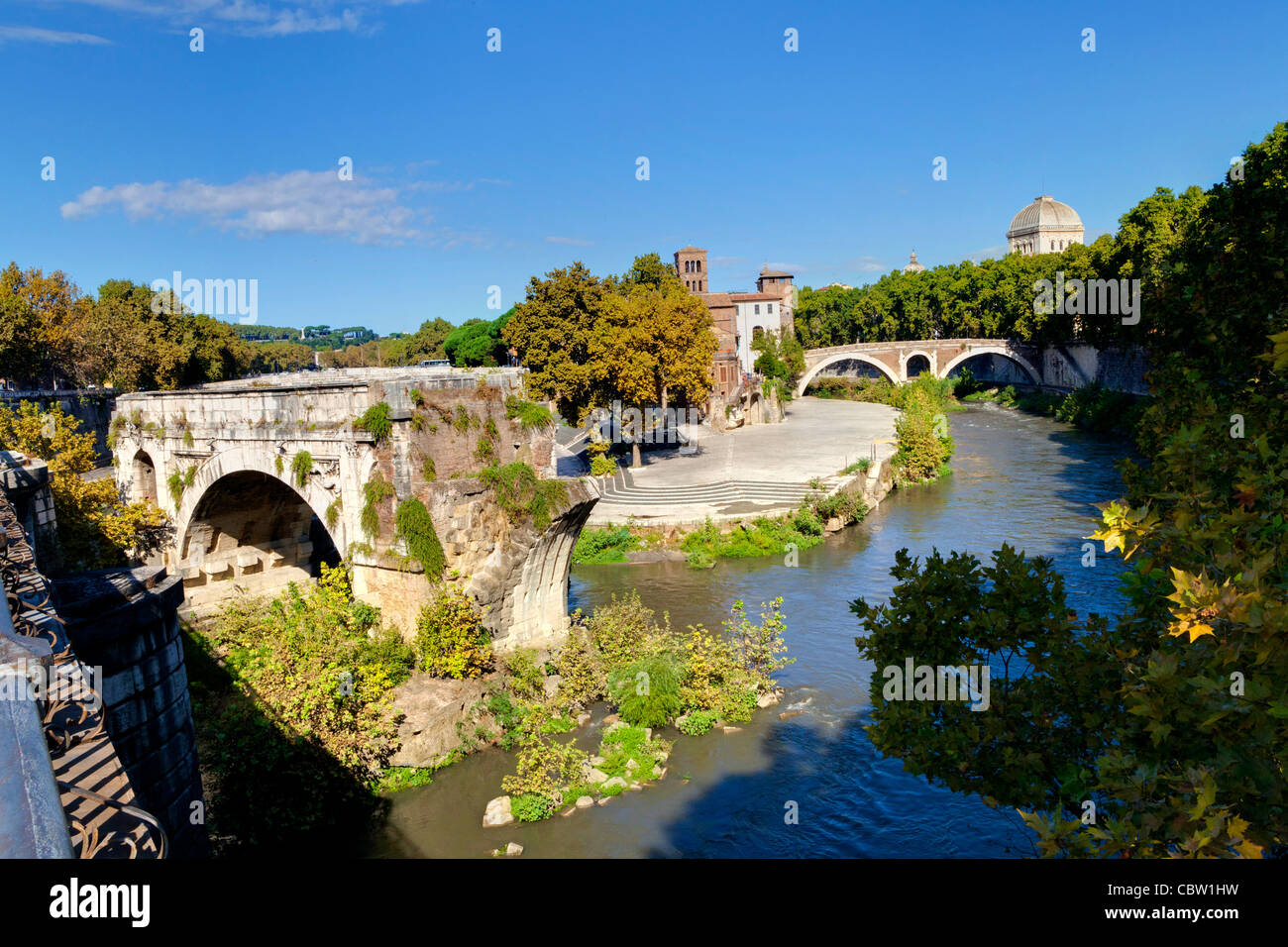 Ancient Pons Aemilius bridge and the Tiber Island Rome Italy - Stock Image