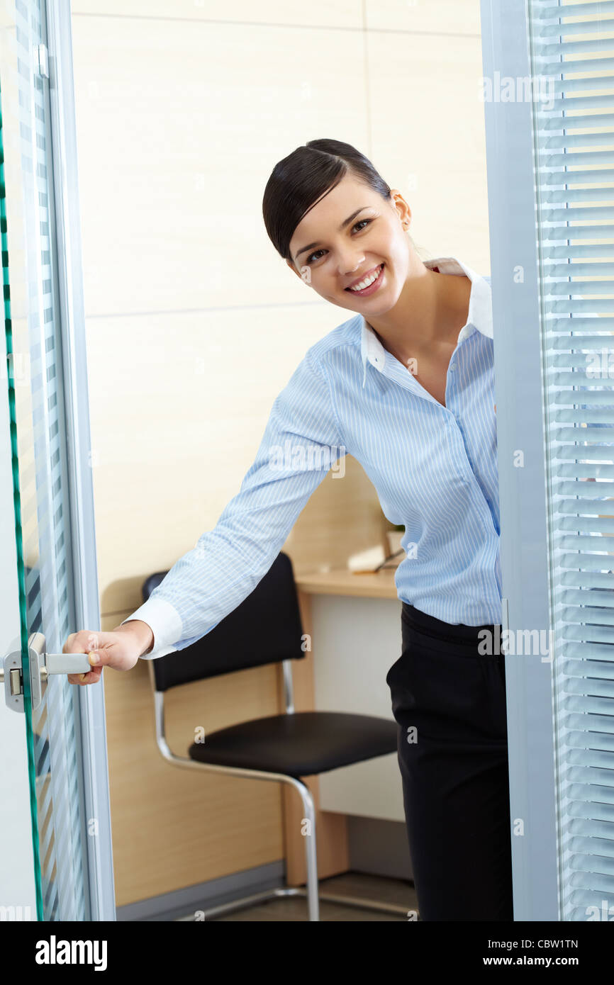 Image of young pretty secretary opening office door and looking at camera Stock Photo