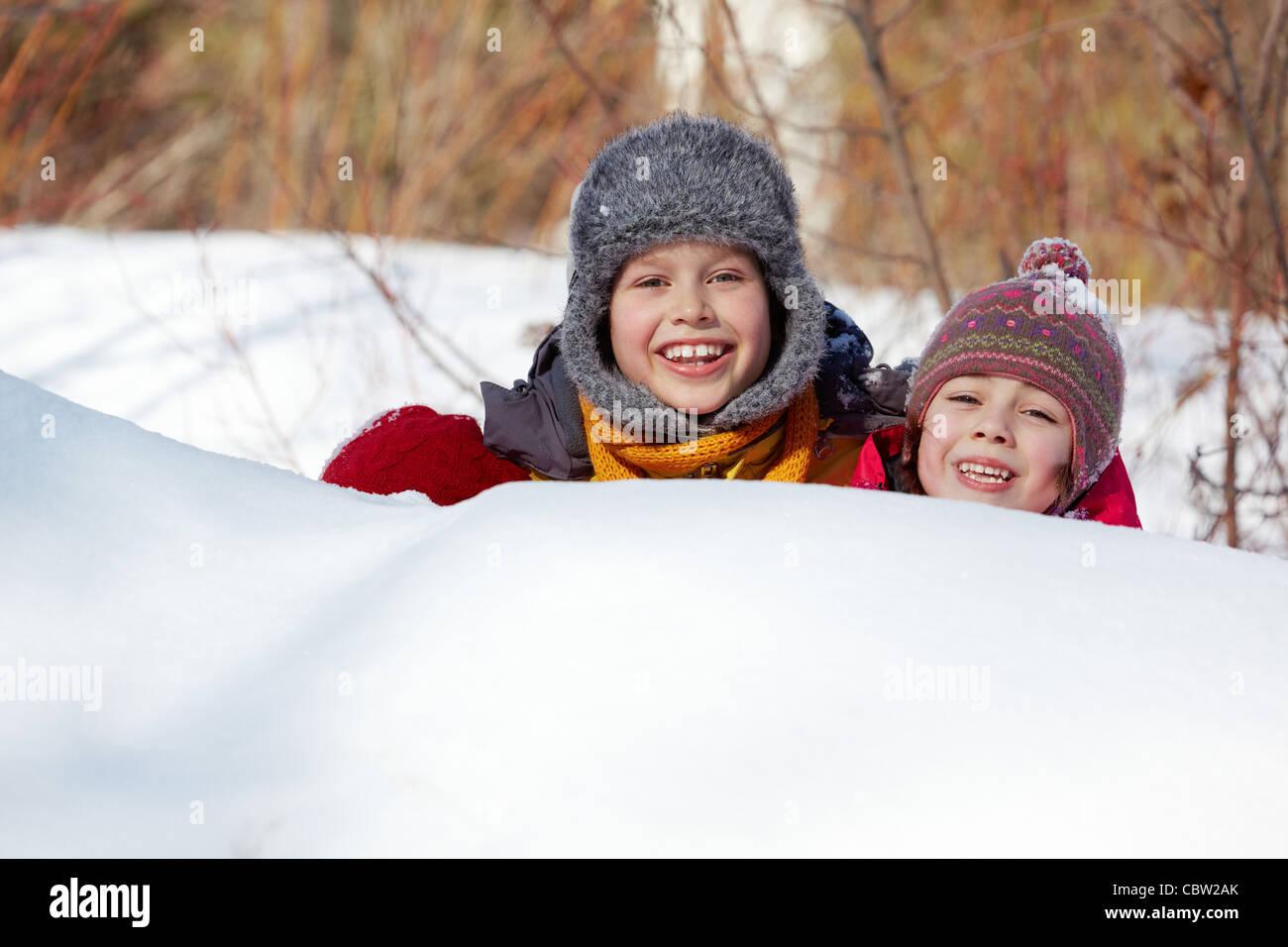 Happy friends in winterwear peeking out of snowdrift outside - Stock Image