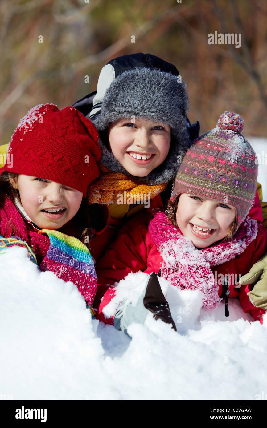 Happy friends in winterwear playing in snowdrift outside - Stock Image