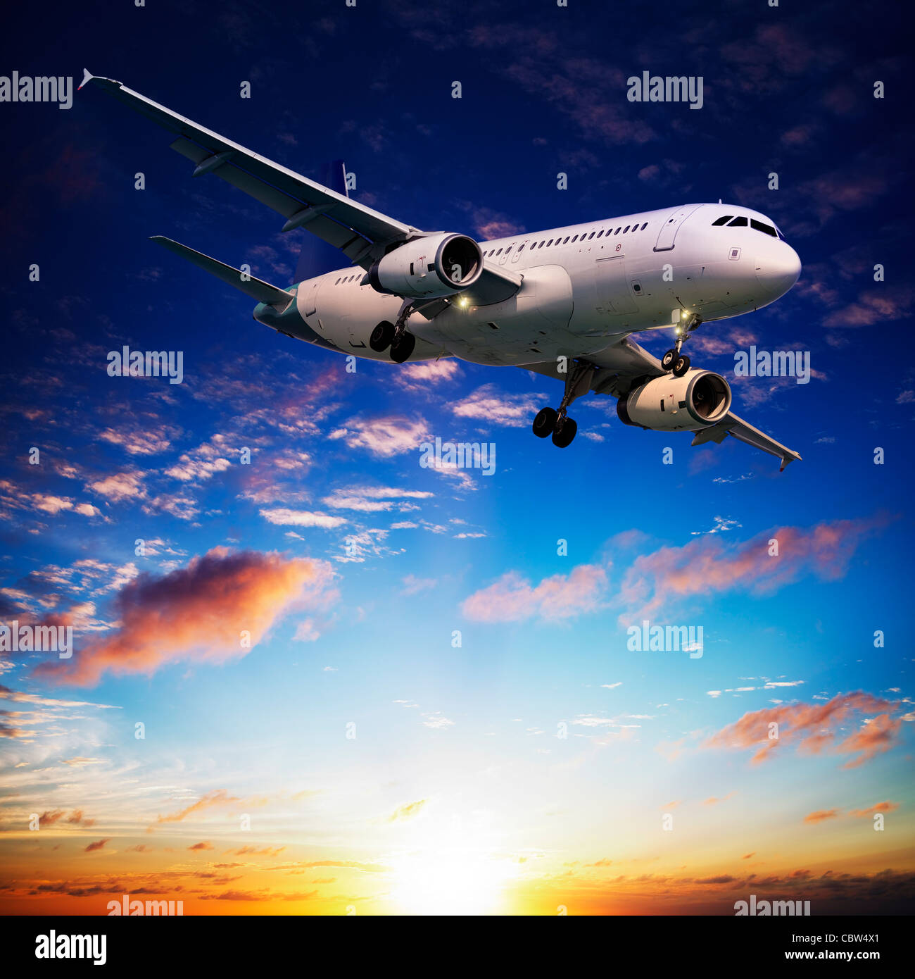 Jet plane in a sunset sky. Square composition. - Stock Image