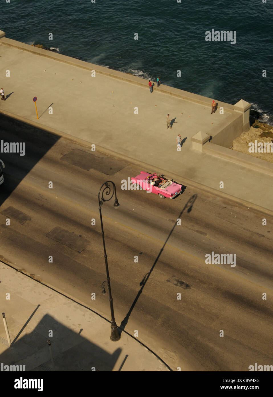 Pink old car crossing Malecon waterfront in old Havana town, Cuba Stock Photo