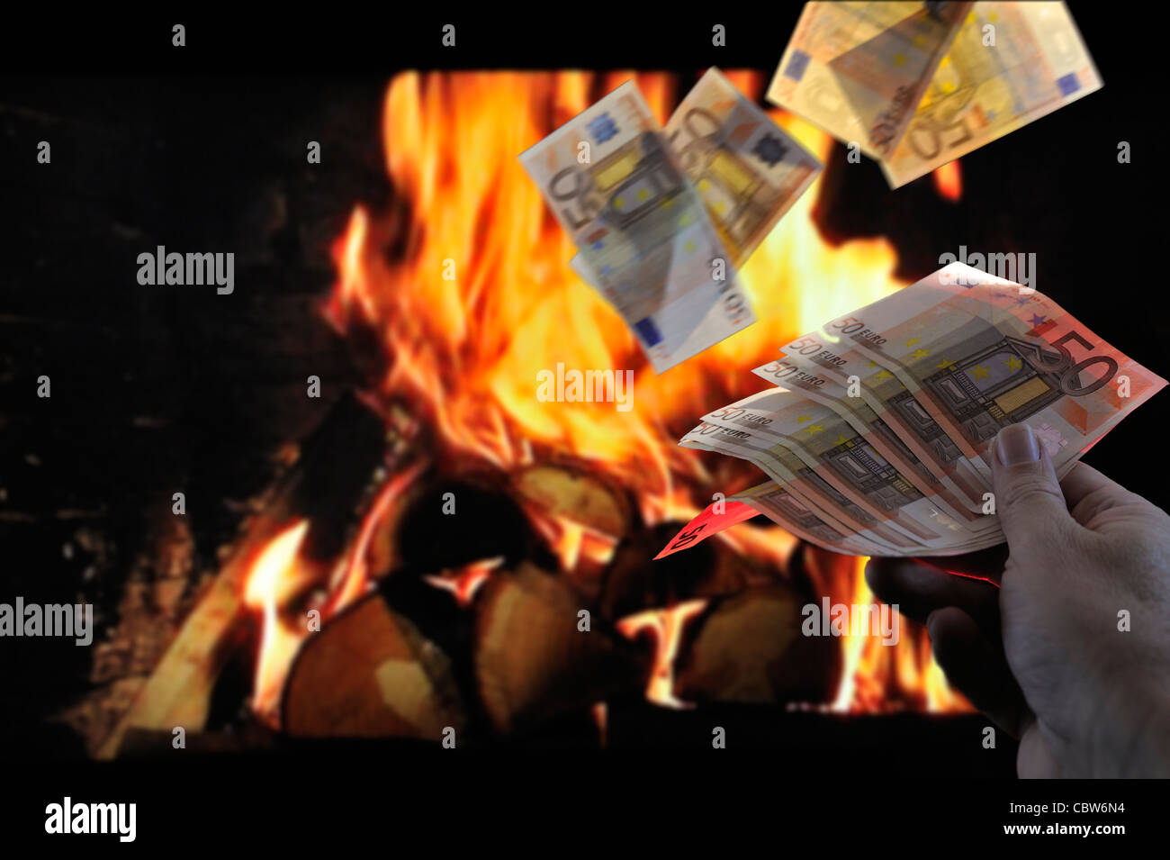 Burning European money by throwing euro bank notes in flames of fireplace to symbolize recession and crisis in the - Stock Image