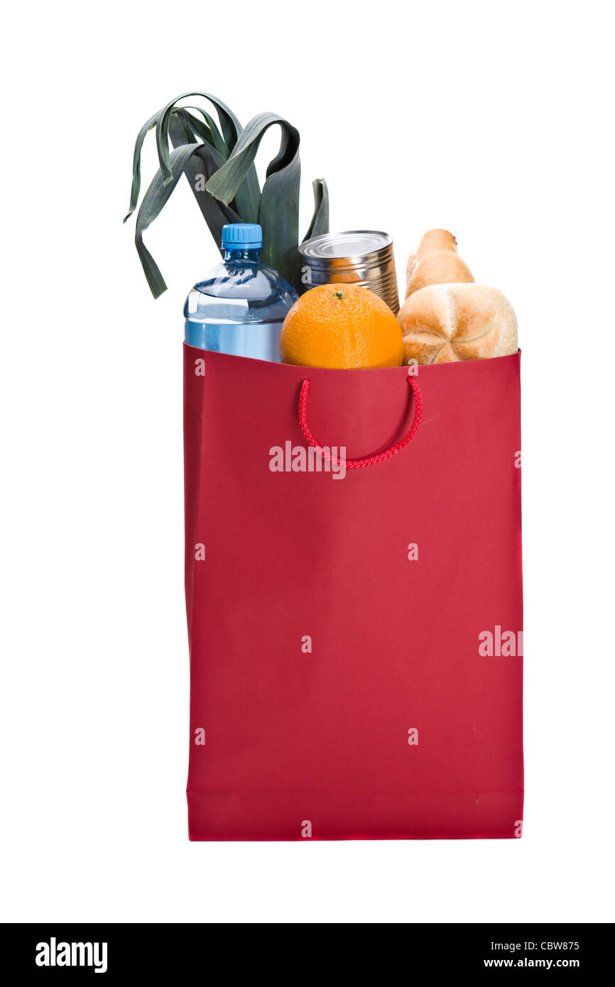 Fresh groceries in a Red bag. Including bread, orange, water, can and leek - Stock Image