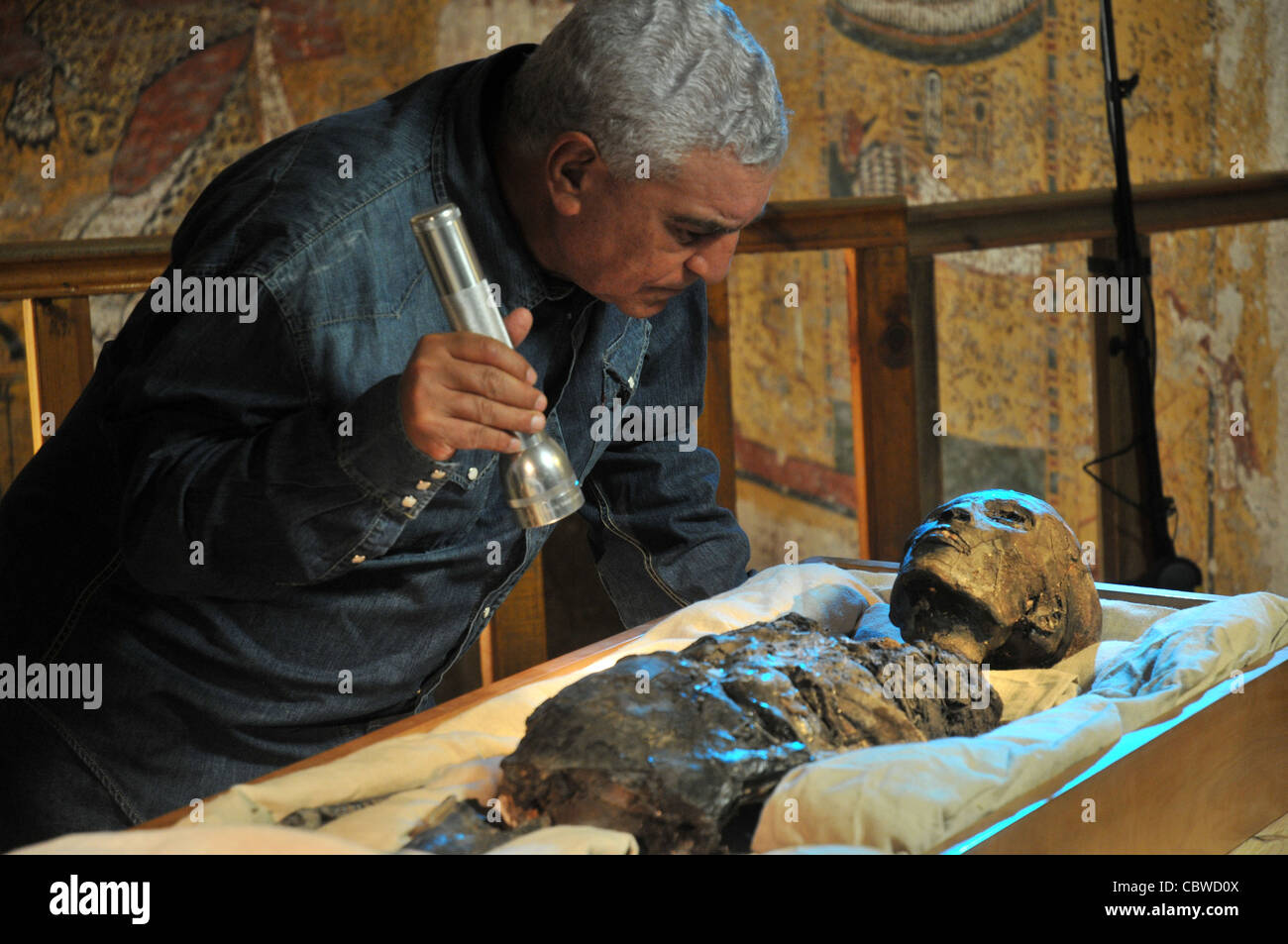 Zahi Hawass examining King Tut mummy inside the tomb of King Tut in the Valley of the Kings in Luxor, Egypt - Stock Image