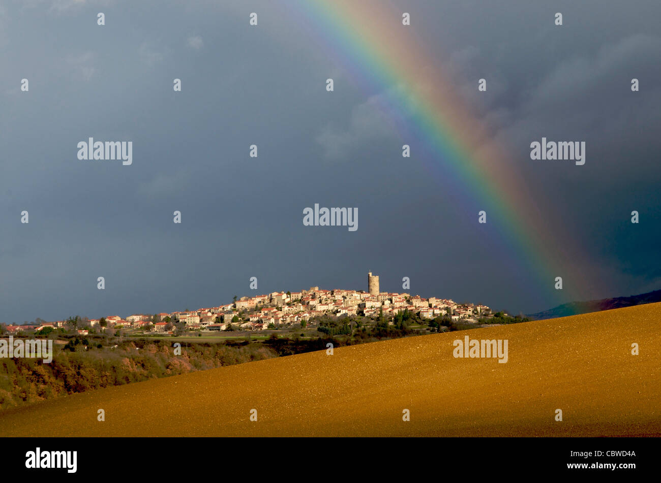 Rainbow over the landscape and village of Montpeyroux, Auvergne, France - Stock Image