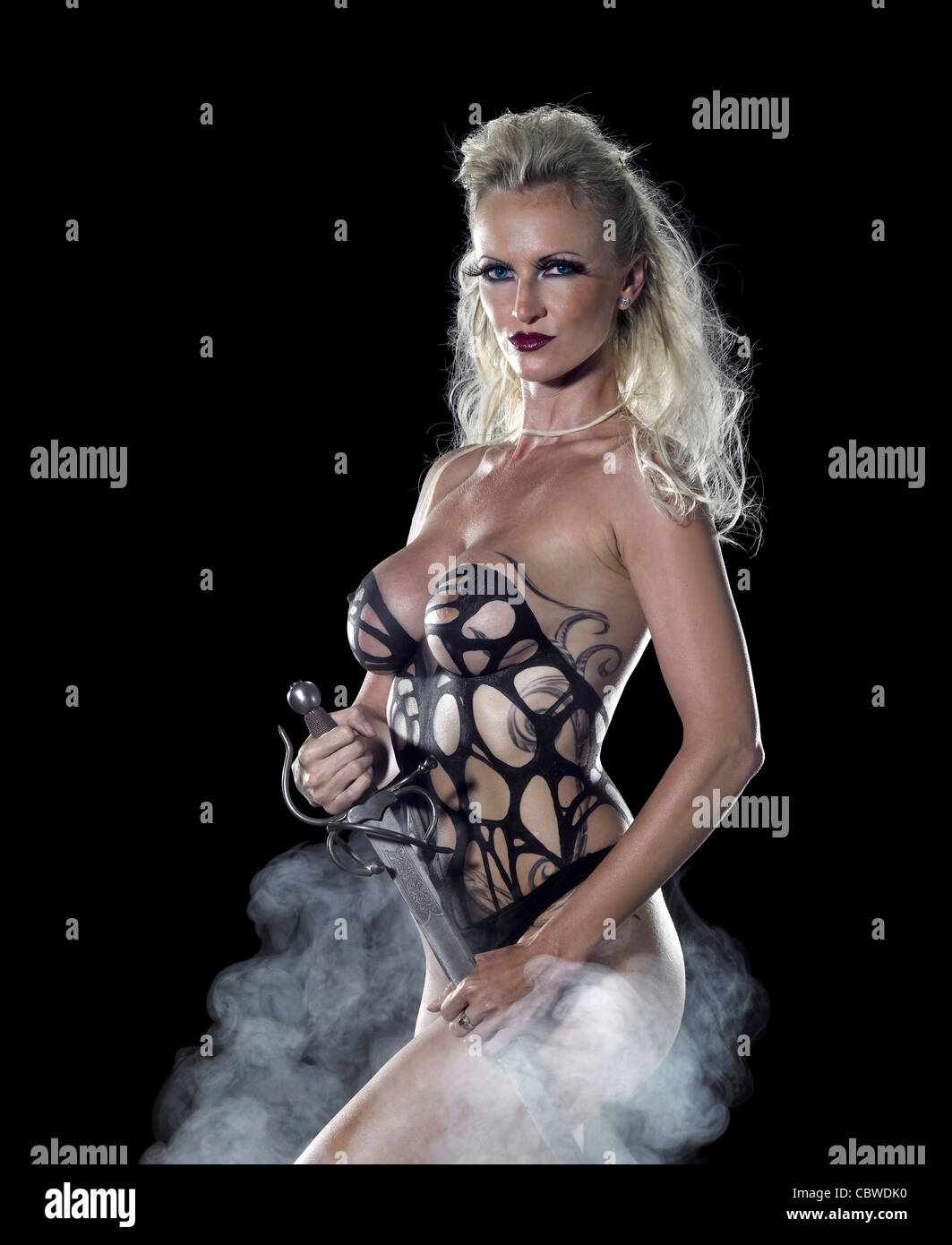 bodypainted blond woman posing in dark back and some fog - Stock Image