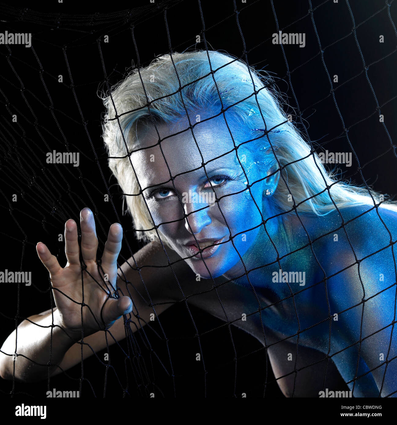 mystic mermaid theme showing a blue bodypainted woman posing with net in black back - Stock Image