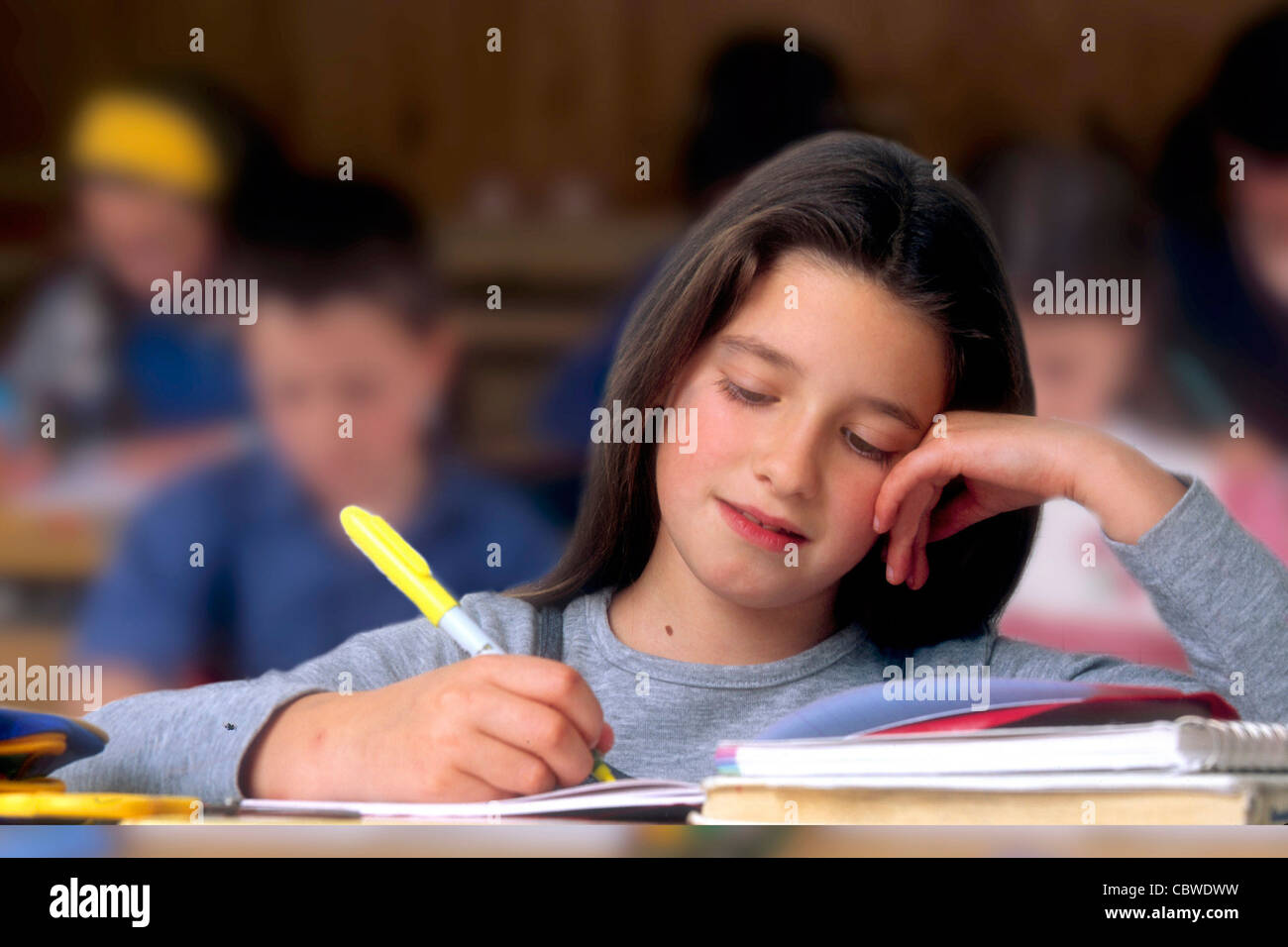 Girl in a classroom - Little girl in a school classroom writing during a lesson. - Stock Image
