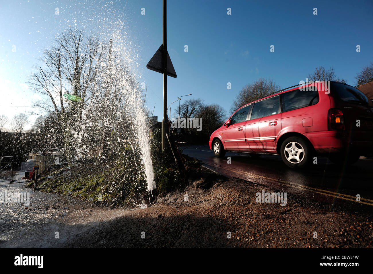 Water leak causing a fountain next to a road - Stock Image