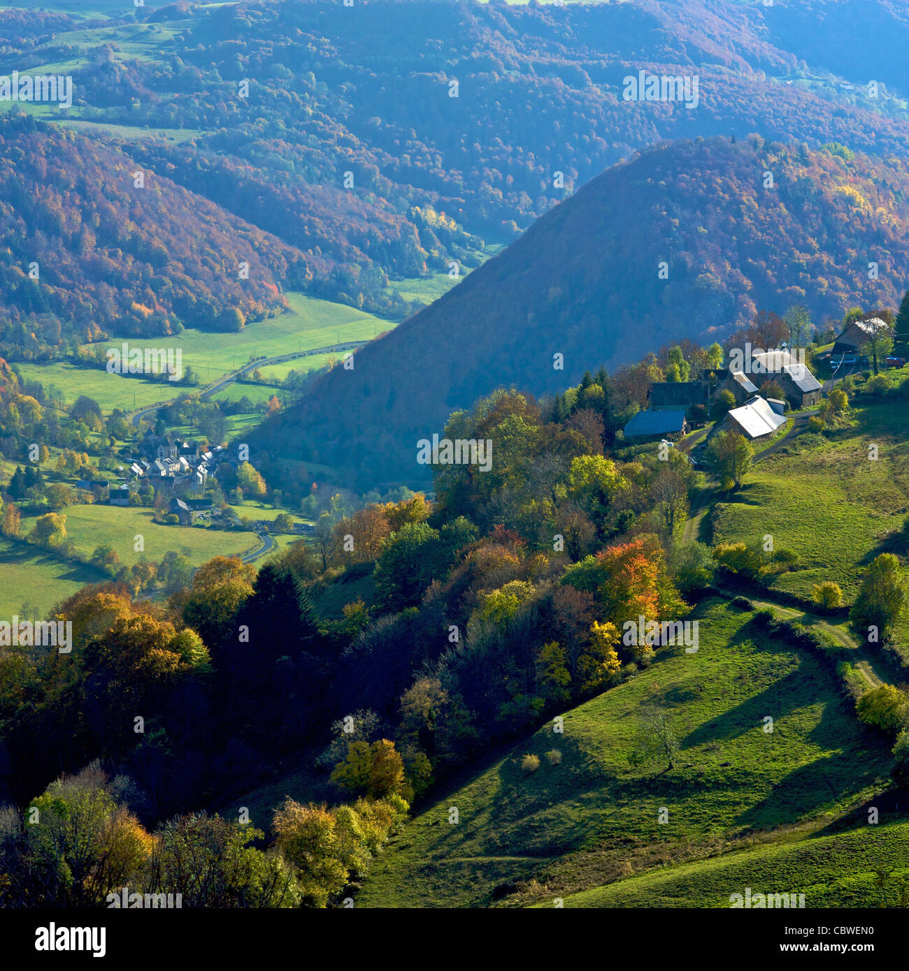 Village at the bottom of a green valley in Auvergne, France. - Stock Image