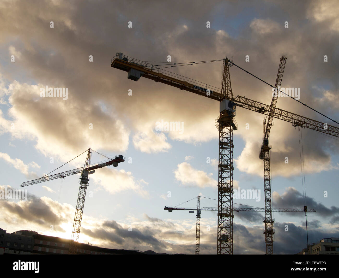 Tall cranes on a construction site - Stock Image