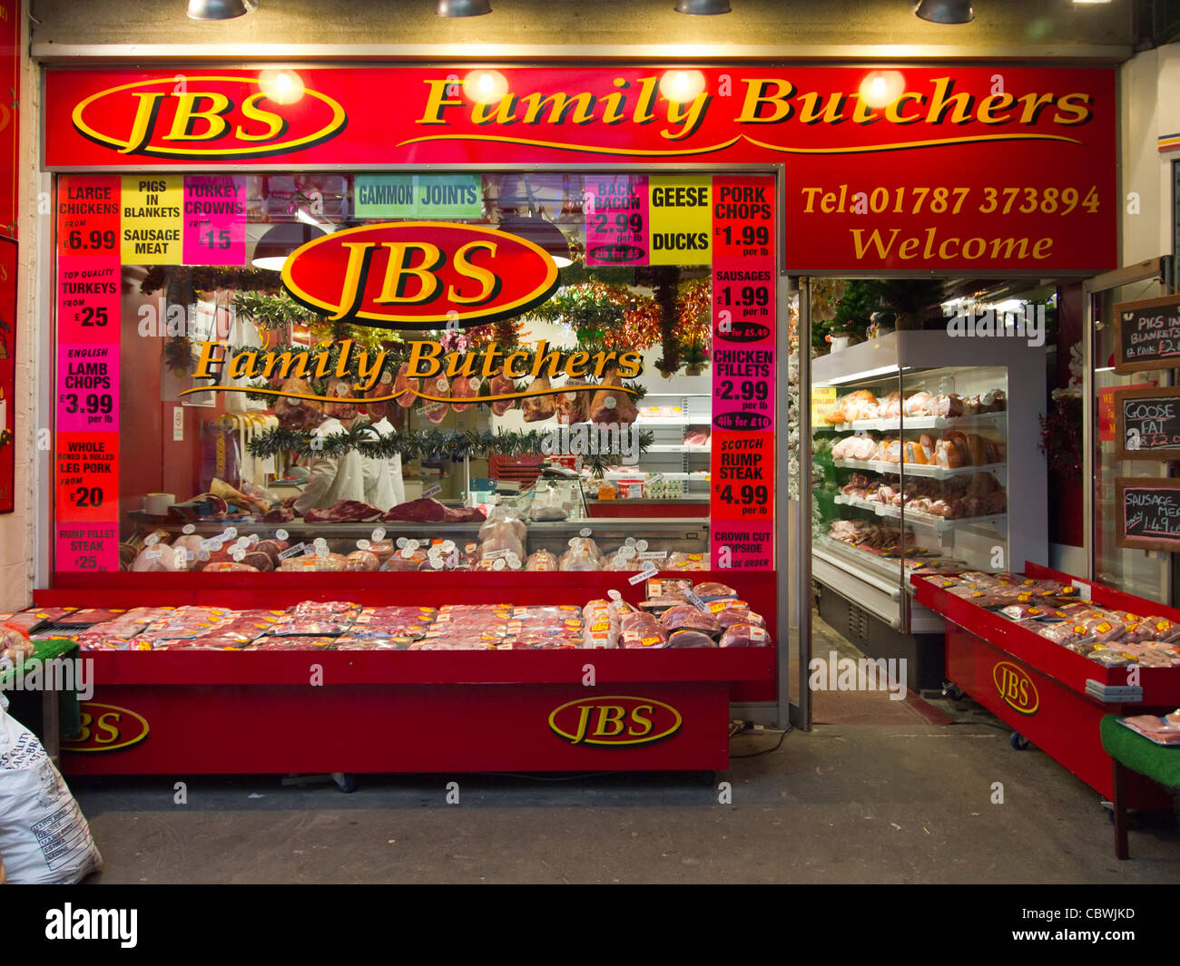 A traditional family-run butcher's shop, with its meat displays, in Sudbury, Suffolk, England. - Stock Image