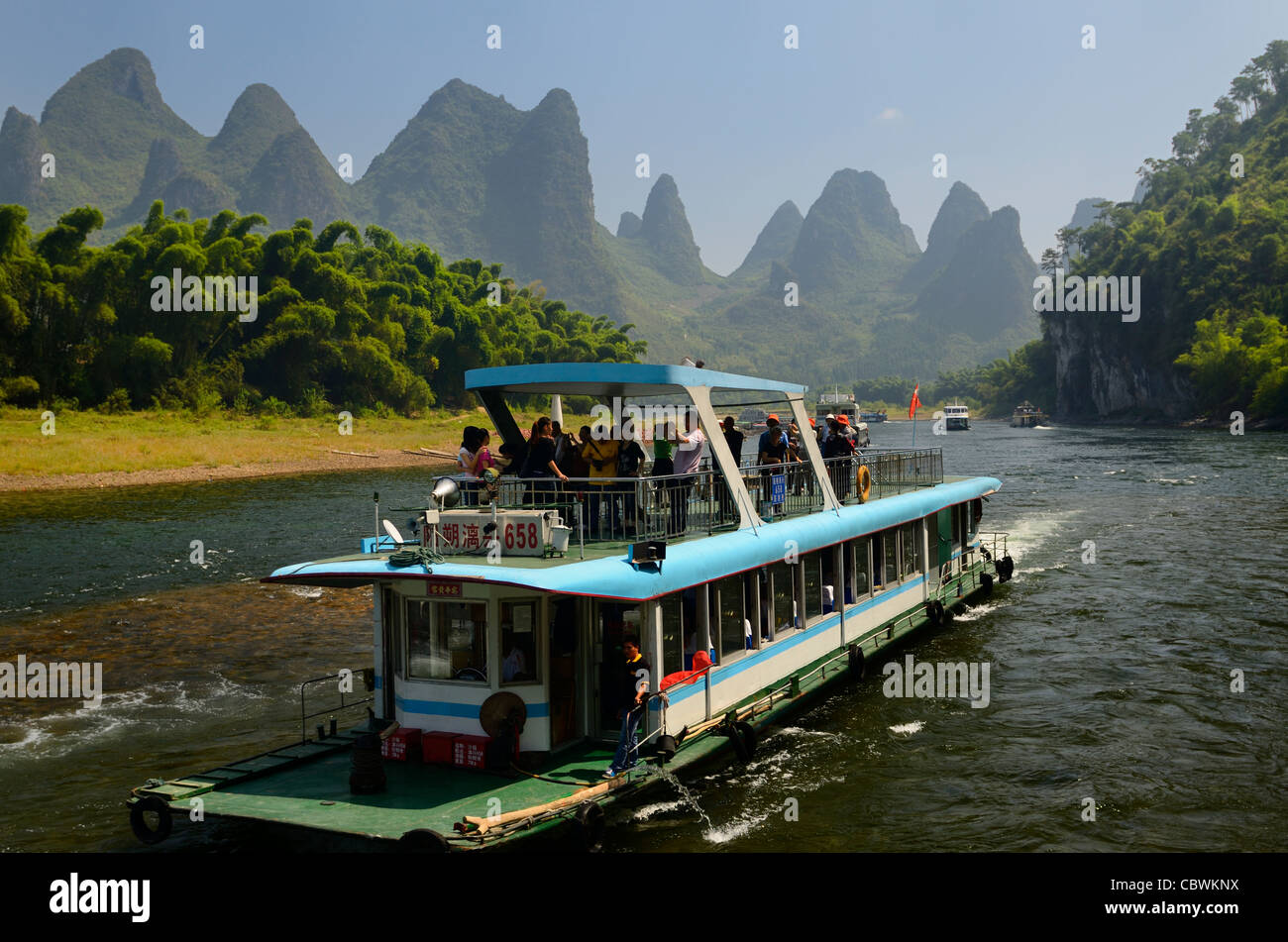 Tour boat cruise down the Li river with bamboo forest and hazy karst peaks Peoples Republic of China - Stock Image