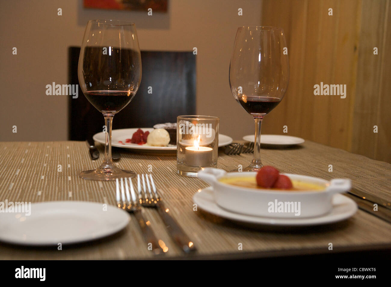 A Table Setting In A Restaurant With Wine Glasses And Dessert Served - Wine glass table setting