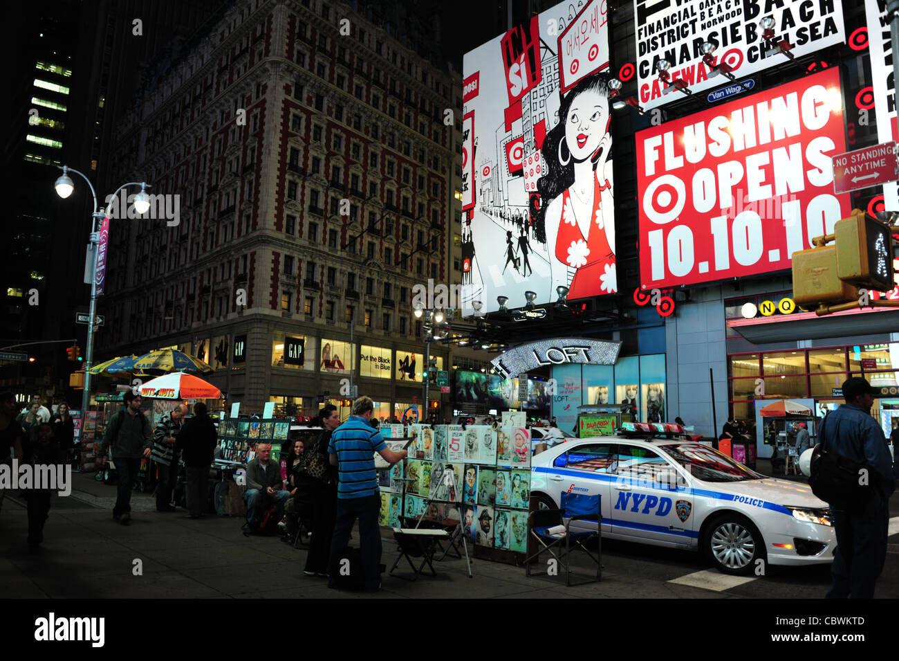 Night neon billboards shot people, NYPD police car parked by sidewalk artwork stall, West 42nd Street at Broadway, Stock Photo