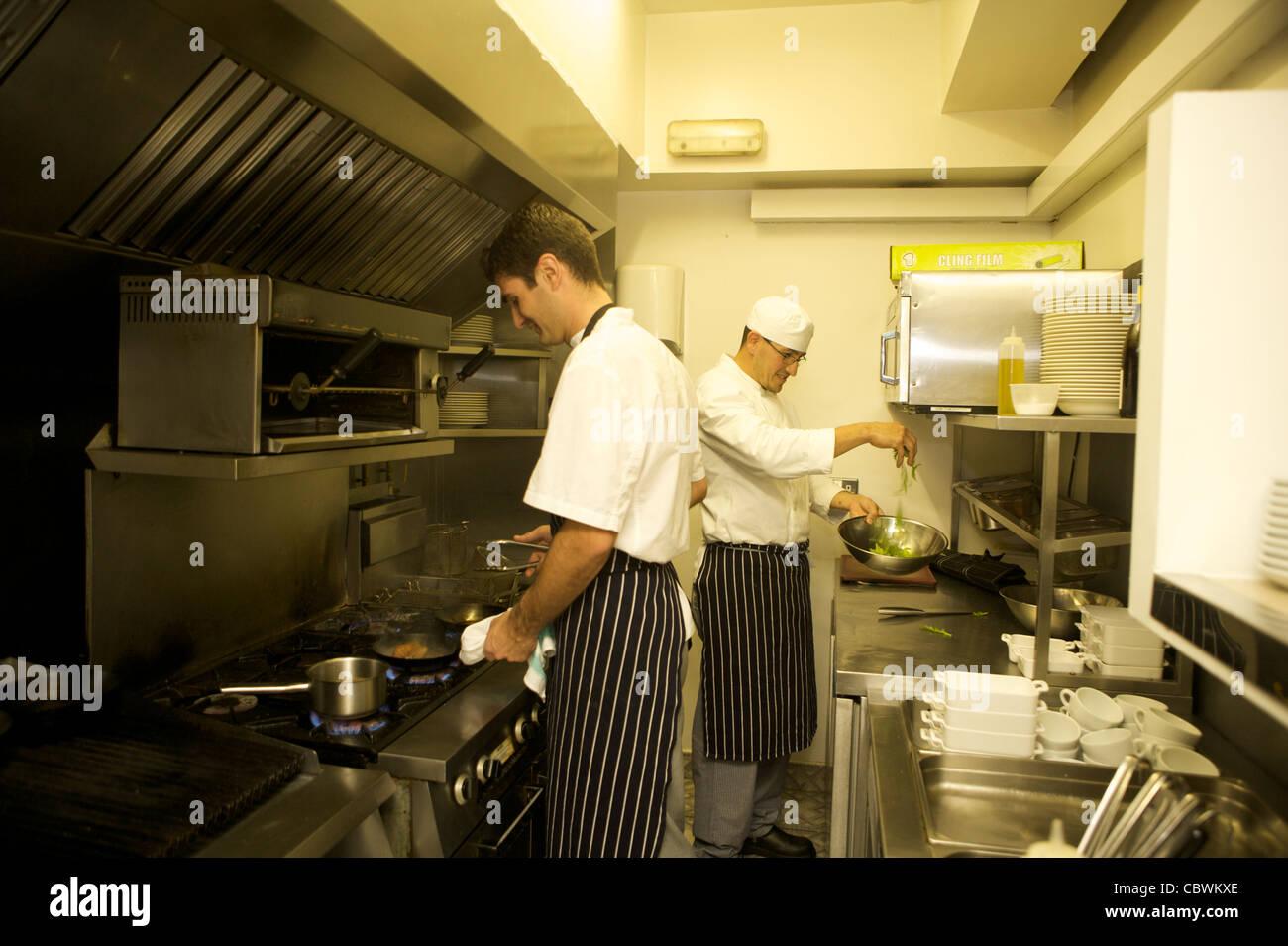 busy restaurant kitchen. Two Chefs Preparing Meals In A Busy Small Restaurant Kitchen