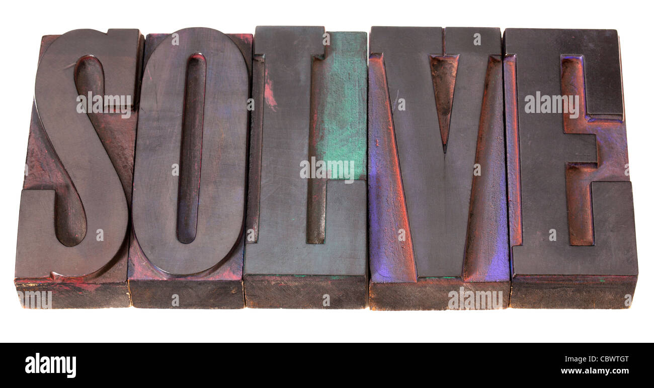 solve word in antique letterpress printing blocks, stained by color inks, isolated on white - Stock Image