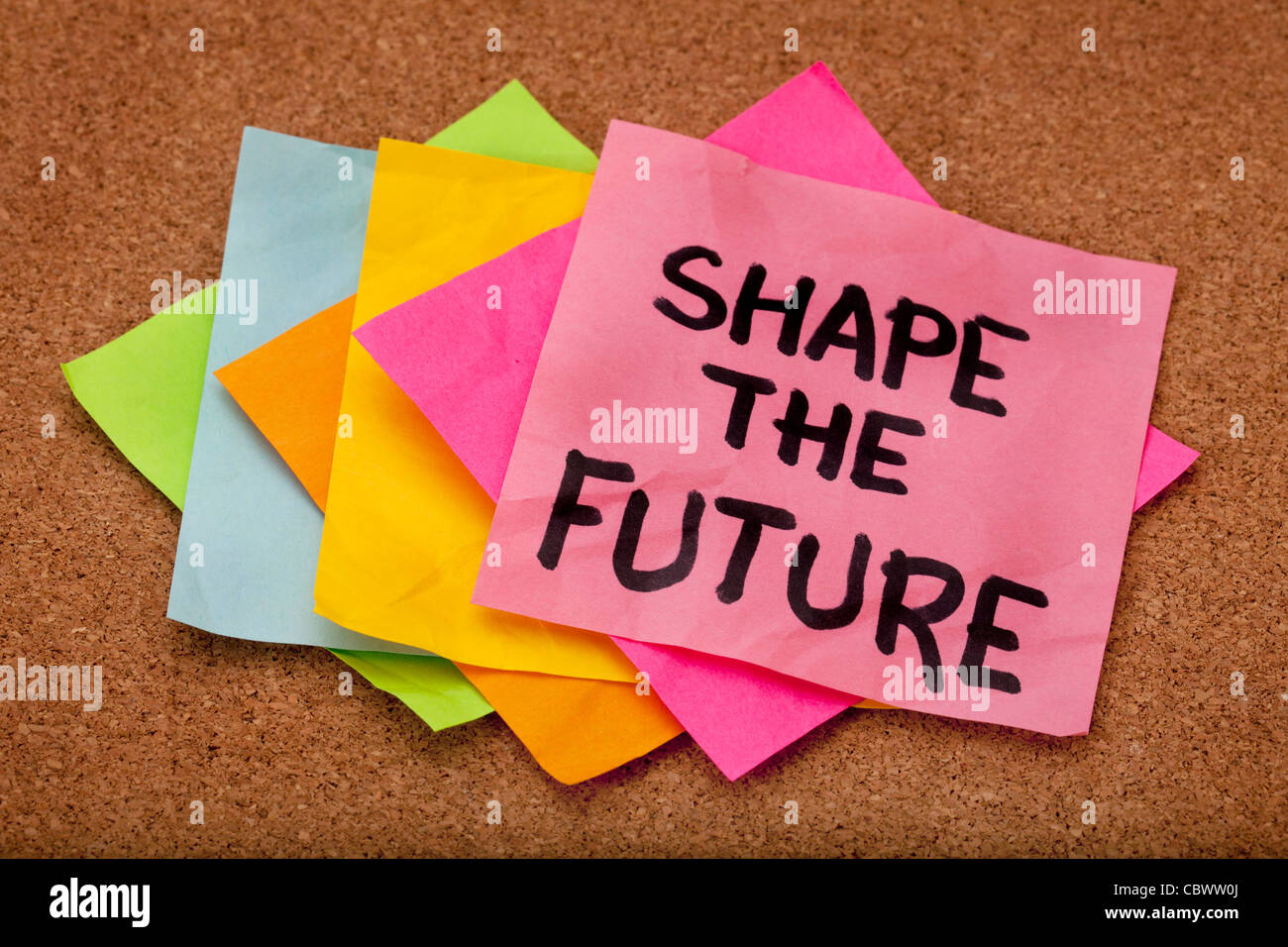 shape the future, motivational slogan, colorful sticky notes on cork bulletin board - Stock Image