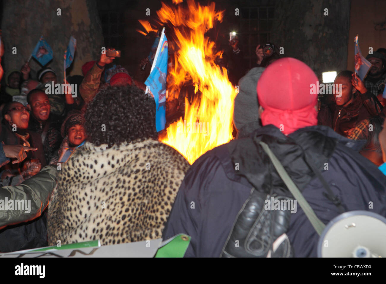 Congolese protesters set alight posters and banners in Whitehall. - Stock Image