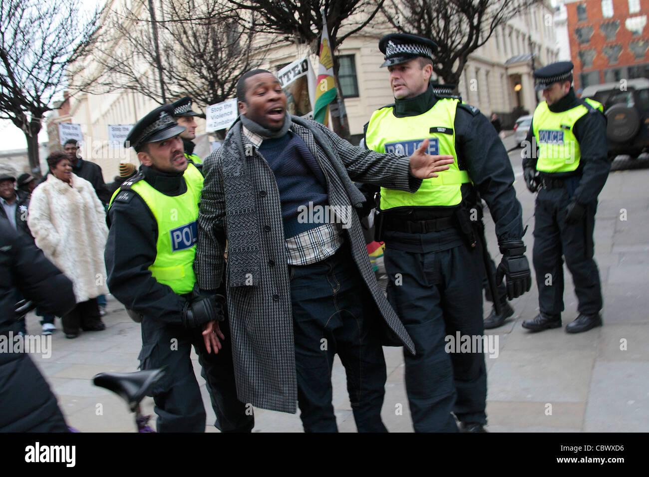 Police tackle Congolese protester - Stock Image