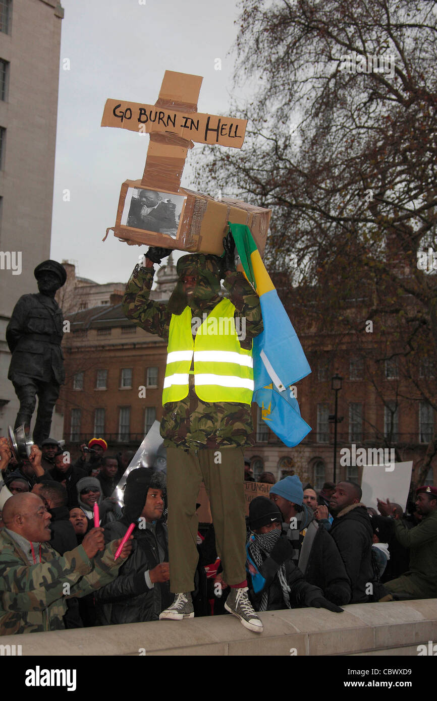 A Congolese protester hold aloft a cardboard coffin in Whitehall. - Stock Image