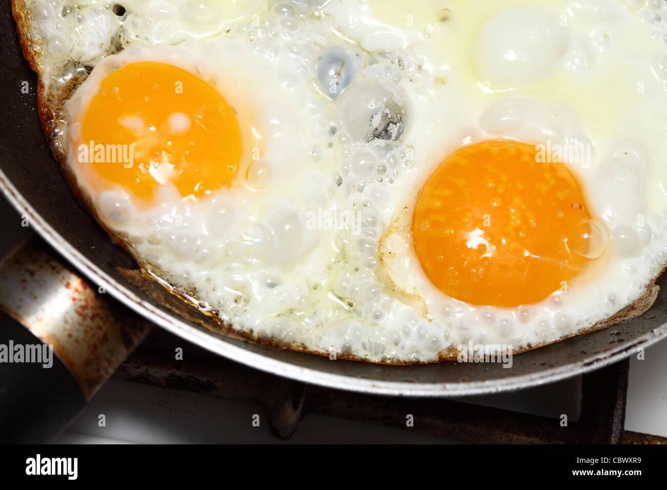 pan full of scramble eggs in a frying pan - Stock Image