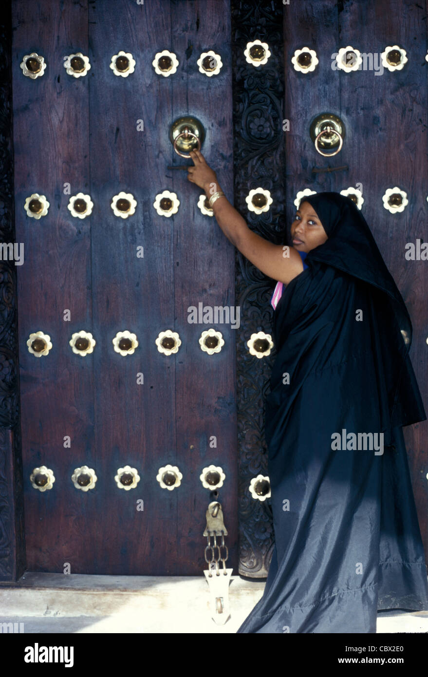 Large carved wooden and brass door in Lamu town with women wearing traditional Arab clothing - Stock Image