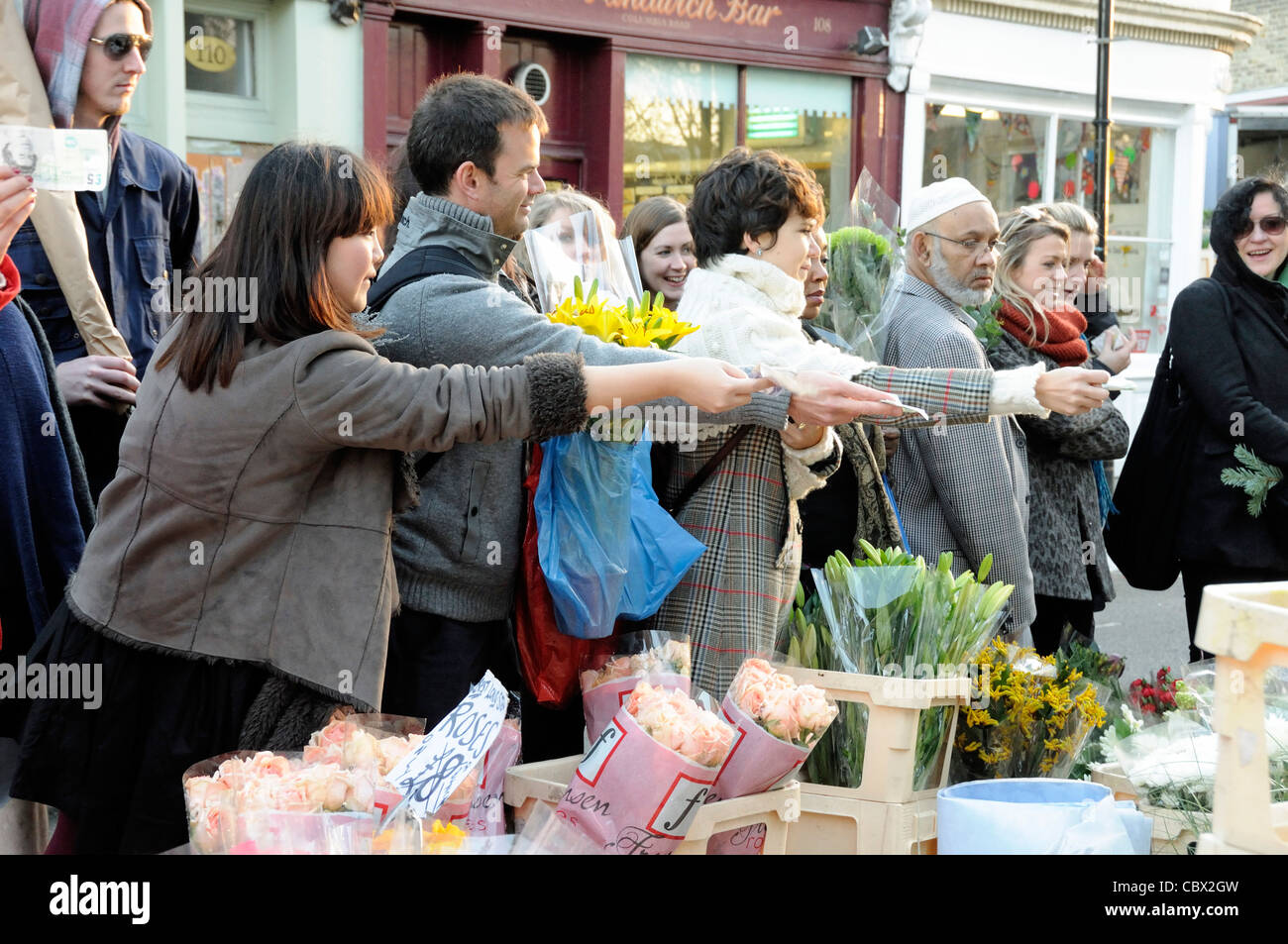 People offer money to the stallholder for cheap bunches of flowers, Columbia Road Flower Market, Tower Hamlets London - Stock Image