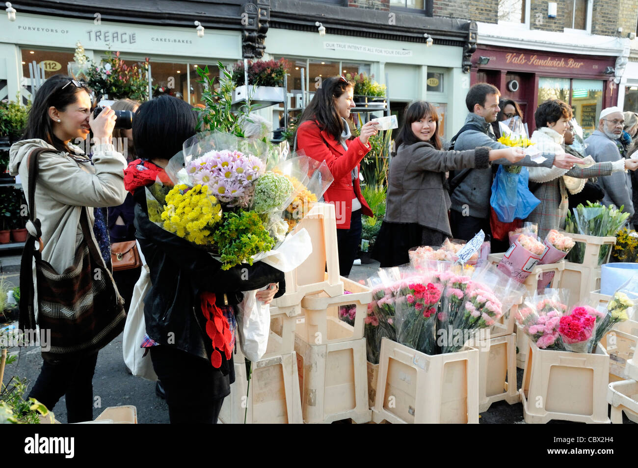 Lady holds several buches of flowers which are being sold off cheaply, Columbia Road Flower Market, Tower Hamlet, - Stock Image