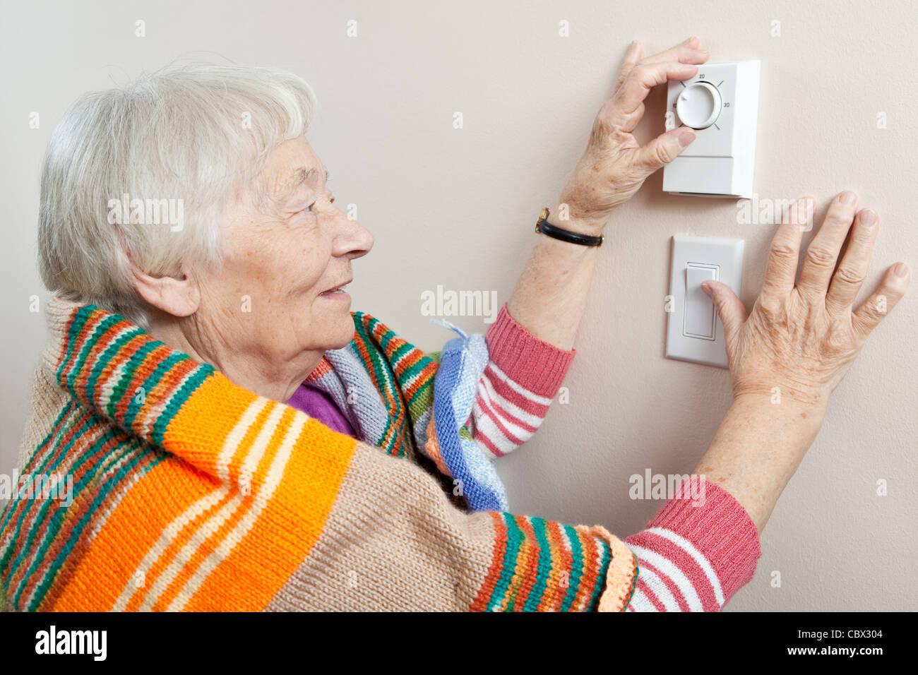 Senior woman adjusting her thermostat - Stock Image