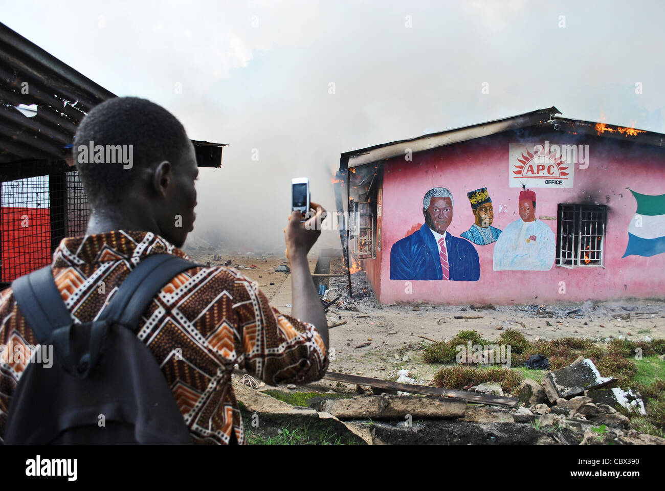 A man uses his phone to photograph the burning office of the APC party during political (pre-election) violence, - Stock Image