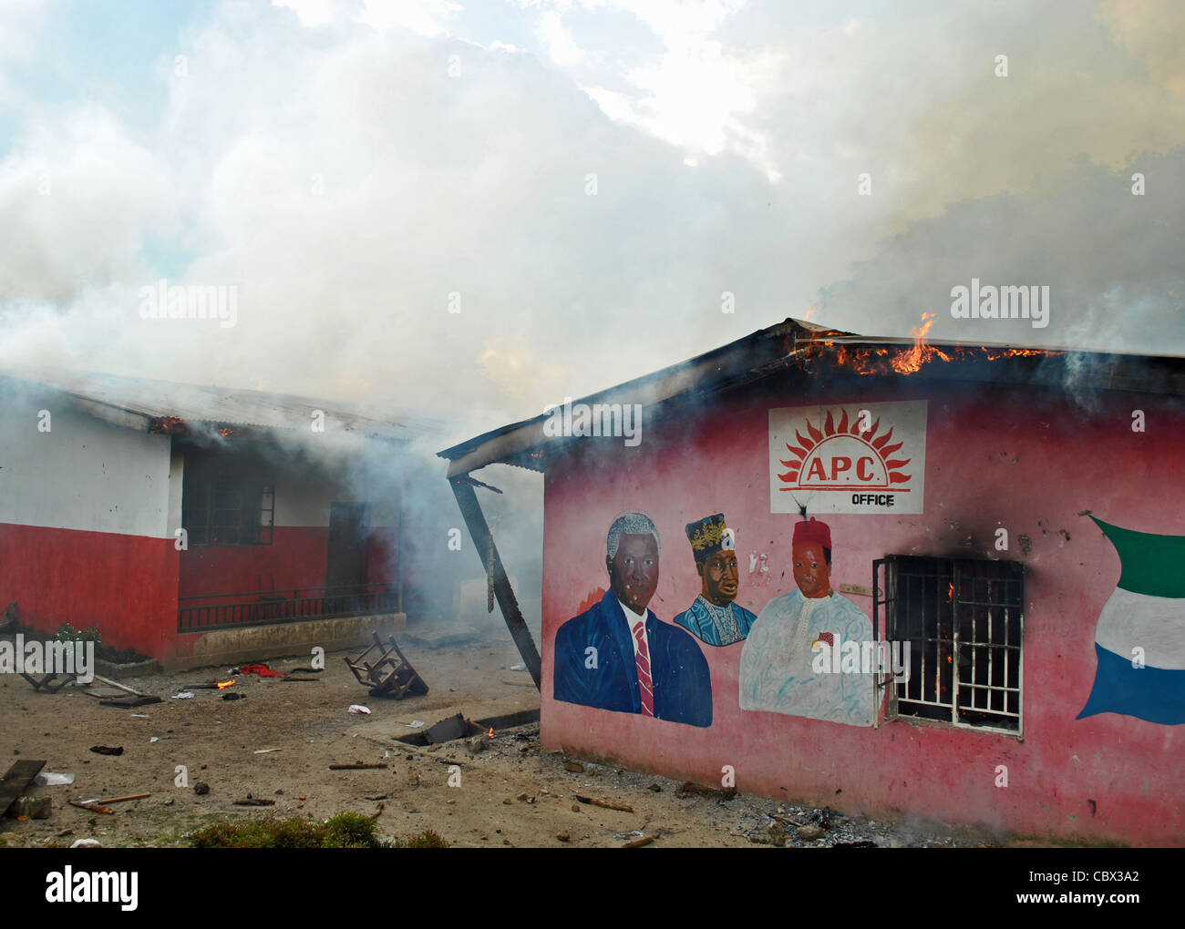 Burning offices of Pres Koroma's APC party, burnt by SLPP supporters at a rally ahead of 2012 elections in Sierra - Stock Image