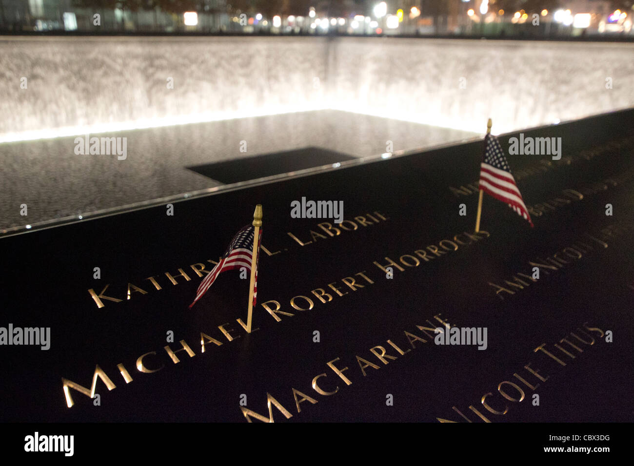 American Flags flank the name of one of the victims of the World Trade Center bombing at the National 9-11 Memorial - Stock Image