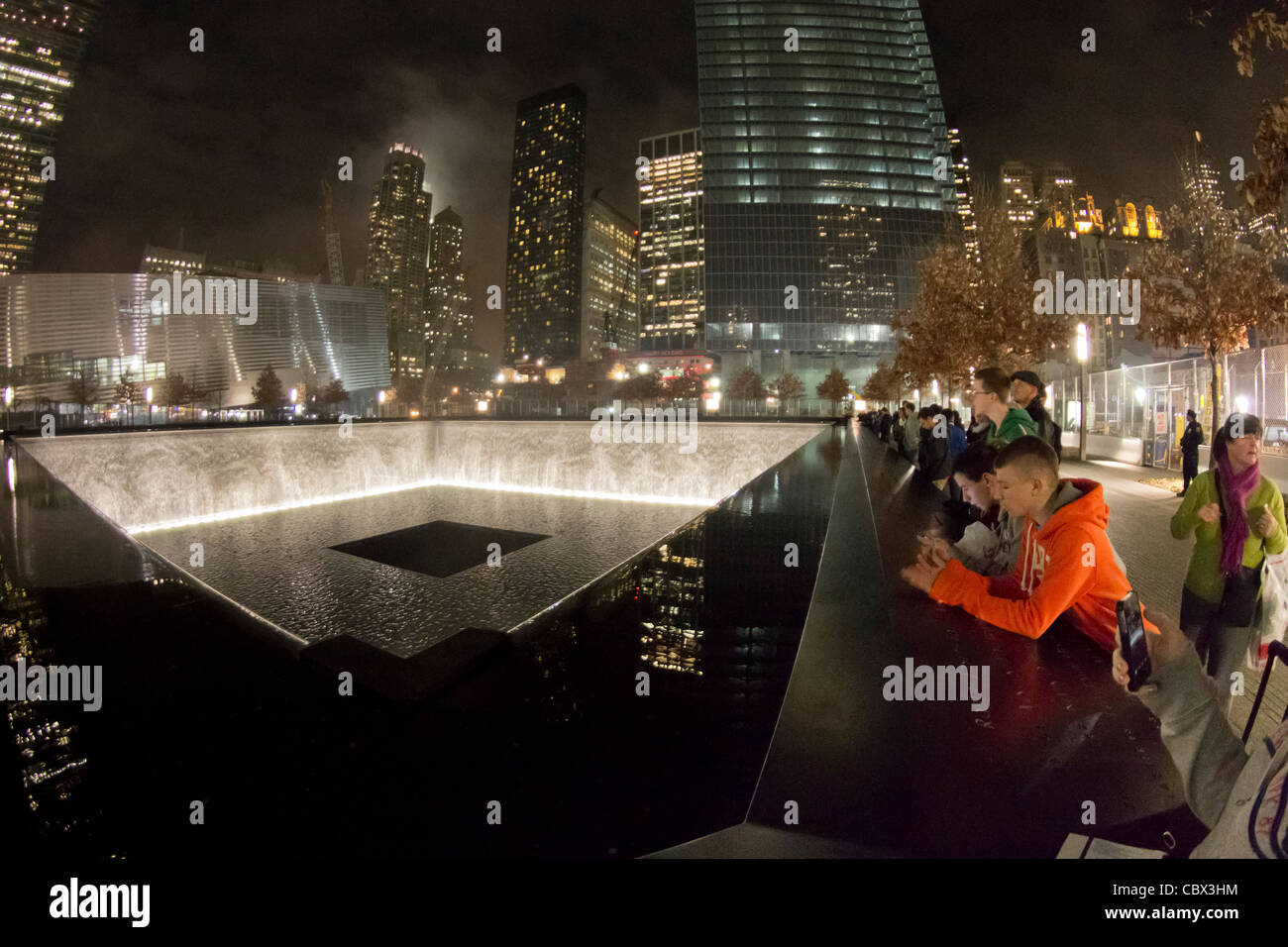 Visitors to the National 9-11 Memorial at Ground Zero view the reflecting pool at the site of the south tower - Stock Image